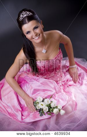 Happy young bride posing in a pink wedding dress holding bouqet of white flowers. stock photo