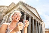 Girl eating frozen yogurt by Pantheon, Rome, Italy. Upbeat visitor lady chuckling getting a charge o