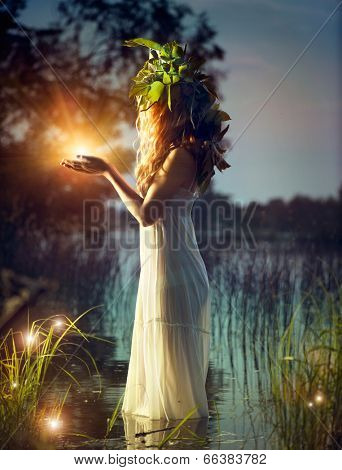 Fantasy young lady taking enchantment light in her grasp. Puzzling Night scene. Witch remaining in t