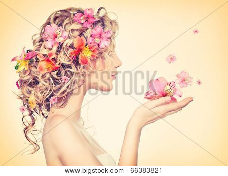 Beauty girl takes beautiful flowers in her hands. Blowing flower. Hairstyle with flowers.  Fantasy g
