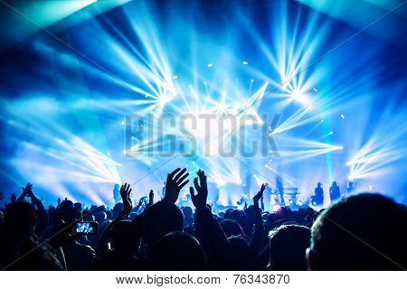 Large group of happy people enjoying rock concert, clapping with raised up hands, blue lights from t