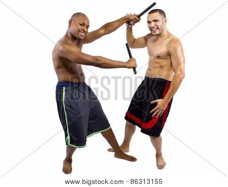 Martial Arts instructor teaching a student the Filipino Martial Art Kali Escrima or Arnis with fighting sticks. stock photo