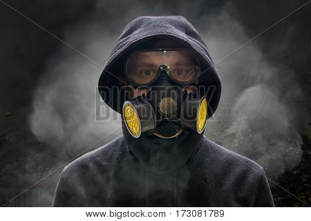 Apocalypse or armageddon concept. Man is wearing gas mask. A lot of smoke in background. stock photo