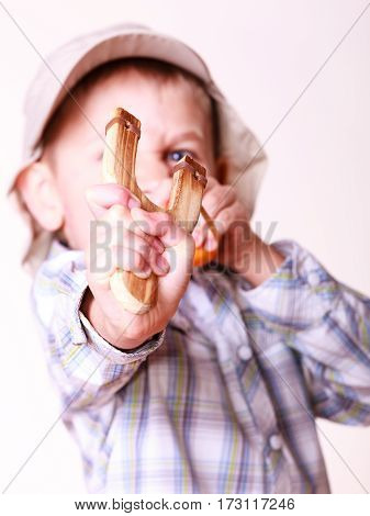Nature and free time prankster little boy. Child have fun with wooden sling shot and fruit aim mandarine. stock photo
