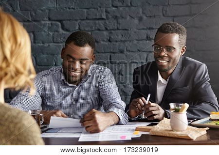 Two dark-skinned employers interviewing young woman with fair hair during job interview. Recruiting expert in suit and his assistant questioning female candidate for position in their company stock photo