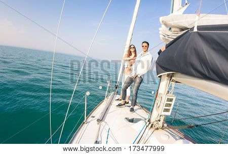 Young couple in love on sail boat having fun with champagne flute glasses - Happy exclusive travel concept on sailboat tour - Boyfriend and girlfriend on luxury cruise - Sunny afternoon color tones