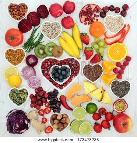Paleolithic diet food of fresh fruit and vegetables, nuts and seeds on distressed white wood background. High in antioxidants, vitamins, anthocyanins and dietary fiber. stock photo