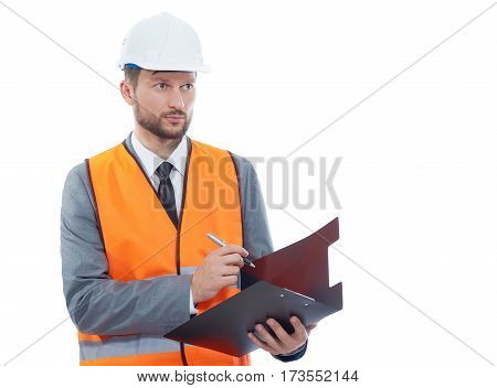 Confident constructionist. Confident male constructionist looking away while making notes on his clipboard copyspace isolated hardhat safety vest wearing occupation building project architectural stock photo