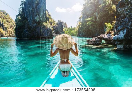 Back view of the young woman in straw hat relaxing on the boat and looking forward into lagoon. Trav