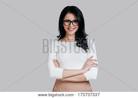 Confident business expert. Beautiful young woman in smart casual wear keeping arms crossed and smiling while standing against grey background stock photo