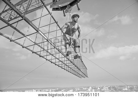 Professional handyman. Low angle black and white shot of a young muscular builder working at construction site looking away attentively working professionalism attention concentration people concept stock photo