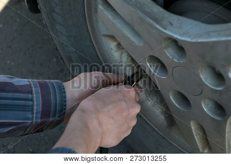 human hands insert the hose of the car pump to pump air into the wheel of the car stock photo