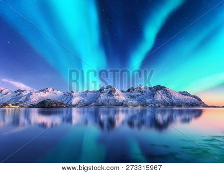 Northern Lights And Snow Covered Mountains In Lofoten Islands, Norway. Aurora Borealis. Starry Sky W
