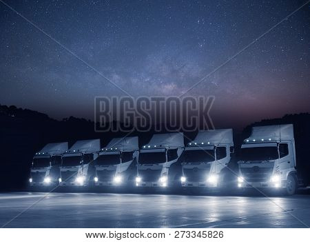 New haulage truck white fleet is parking at night with astronomy milkyway on teh sky landscape view. stock photo