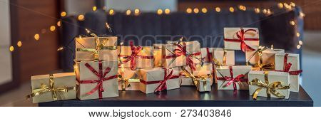 Many Gifts On A Black Wooden Table For Any Holiday. Present Wrapped In Craft Paper With A Red And Go