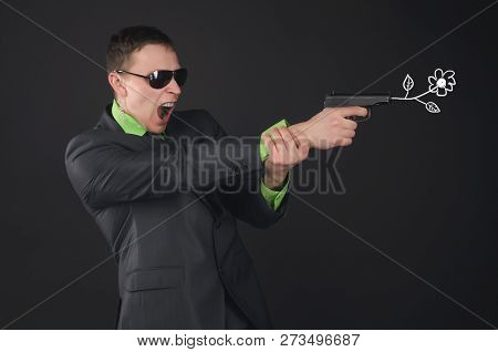 Security agent man or spy is shooting from a gun by a flower isolated on black background. stock photo