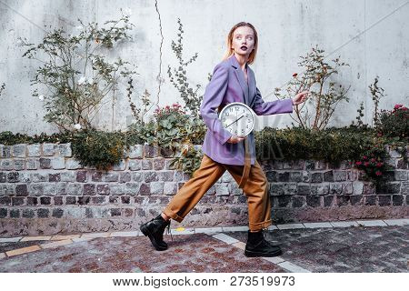Slim model with dark lips wearing orange trousers and purple jacket stock photo