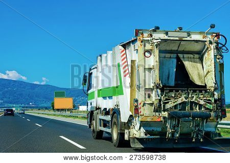 Truck carrying trailer with garbage container at the asphalt road in Slovenia. stock photo