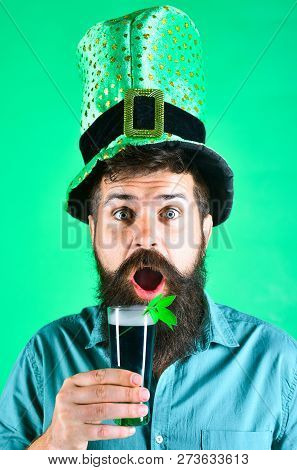 St Patrick's Day. Surprised man holds glass of beer on St.Patrick's day. Saint Patrick's Day concept - bearded man in leprechaun hat pours beer. St Patrick's Day green beer with shamrock. Copy space. stock photo