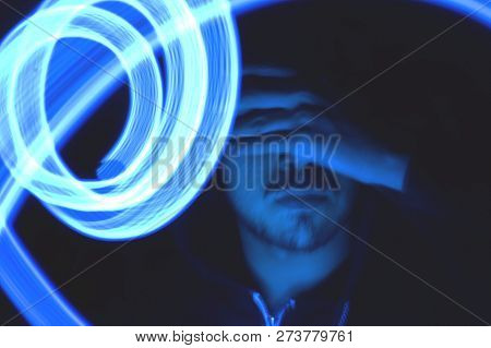 Man hiding her face with hand. Light paiting blue concept. Technology visual. stock photo