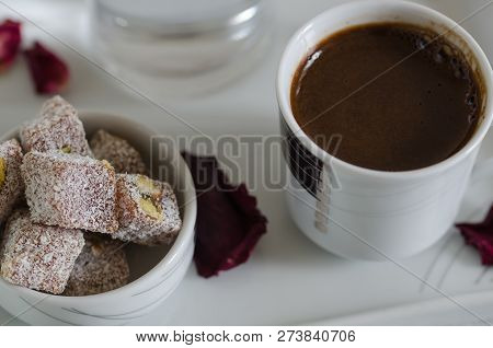 Turkish coffee and Turkish delight with pistachio nuts in white porcelain bowl ,selective clarity,shallow depth of field stock photo