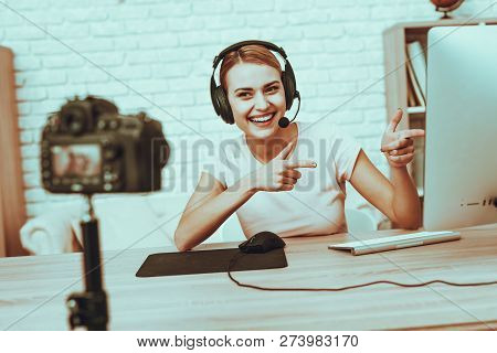 Blogger Makes a Video. Blogger is Gamer is Smiling Woman. Camera Shoots a Video. Woman in Headphones Playing a Video Game on Computer. Woman Looking in Camera and Pointing at Monitor. Studio Interior. stock photo