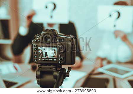Blur View of Bloggers Makes a Video. Bloggers is Man and Woman. Video About a Business. Camera Shoots a Video. Gadgets and Supplies on Table. People Showes a Question Marks. People in Studio Interior. stock photo