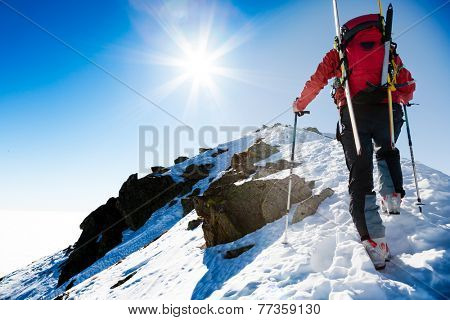Mountaineer walking up along a snowy ridge with the skis in the backpack. In background a shiny brig