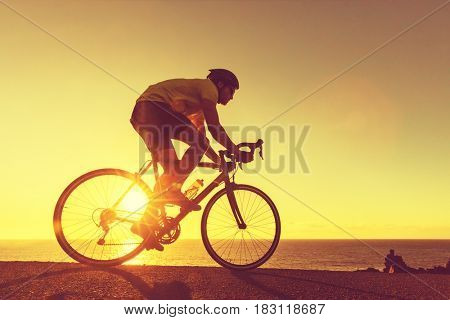 Road bike cyclist man cycling. Biking Sports fitness athlete riding bike on an open road to the suns