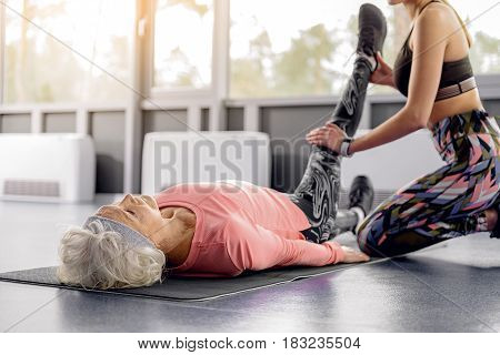 Old woman demonstrating composure while doing stretching in fitness center stock photo