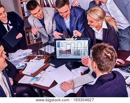Business people office life of team people working with papers sitting table . Cabinets with folders and jalousie, flowers in pots background. Schemas and diagrams on computer monitor. stock photo