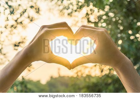 Female hands in the form of heart against sunlight in sunset sky twilight time. Hands in shape of love heart Love concept.