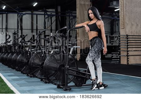 Young attractive woman using exercise bike at the gym. Fitness female using air bike for cardio workout at fitness gym.Sports brunette posing near a row of bicycles in the gym stock photo