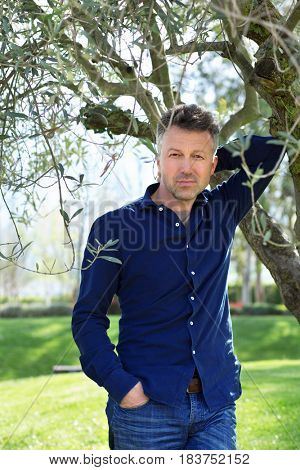 Man in olive grove, image toned. Portrait of handsome mature man lokking at camera over nature background. stock photo