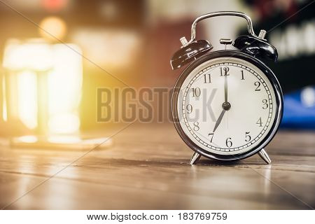 7 o'clock time retro clock on wood table with sun light background stock photo