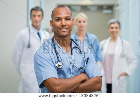 Confident male nurse in front of his medical team looking at camera. Smiling african young surgeon standing in front of his colleagues with folded arms. Multiethnic doctor with staff in background. stock photo