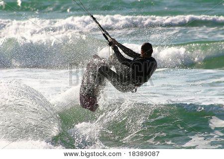 Non identifié kitesurfer saute au-dessus de l'eau au cours de surf sur la mer méditerranée.