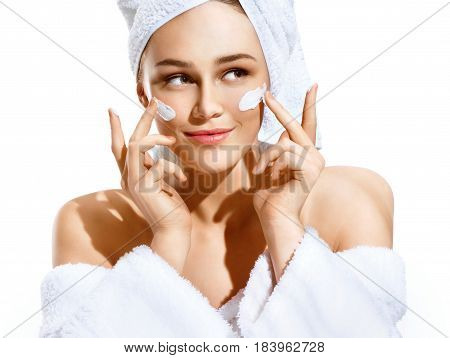 Dazzling young woman applying moisturizing cream on her face. Photo of woman in white bathrobe and towel on white background. Skin care concept stock photo
