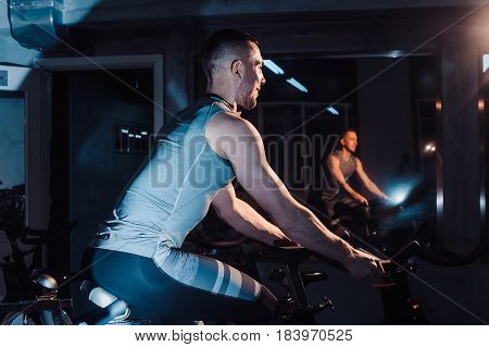 young man riding an exercise bike. The guy is exercising on a stationary bike. in side another view stock photo