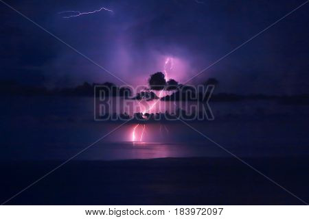 Beautiful dramatic landscape, bright pink lightning over water, storm in the sea, autumn weather, amazing natural wallpaper stock photo