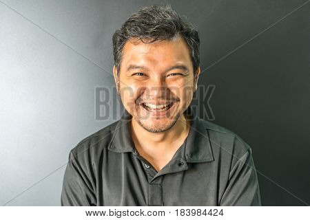 Asia man 40s in black polo shirt have a laughing smile gesture with joyful and happy concept on black background dark style stock photo