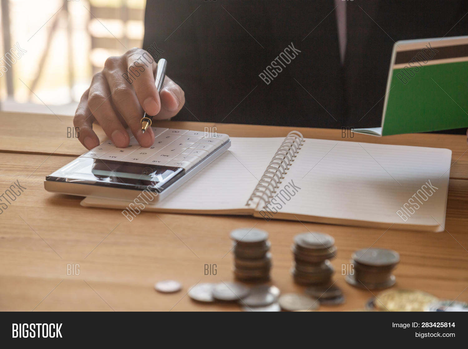 Accountant working on calculator to calculate accounting and business finance plan sales. Business accounting, business investment advisor consulting on the financial report, plan a marketing plan at business office. Business accounting plan concept.