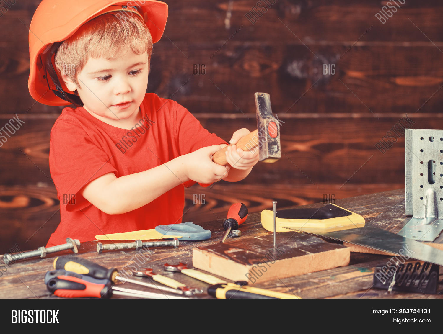 Handcrafting Concept. Toddler On Busy Face Plays With Hammer Tool At Home In Workshop. Kid Boy Play