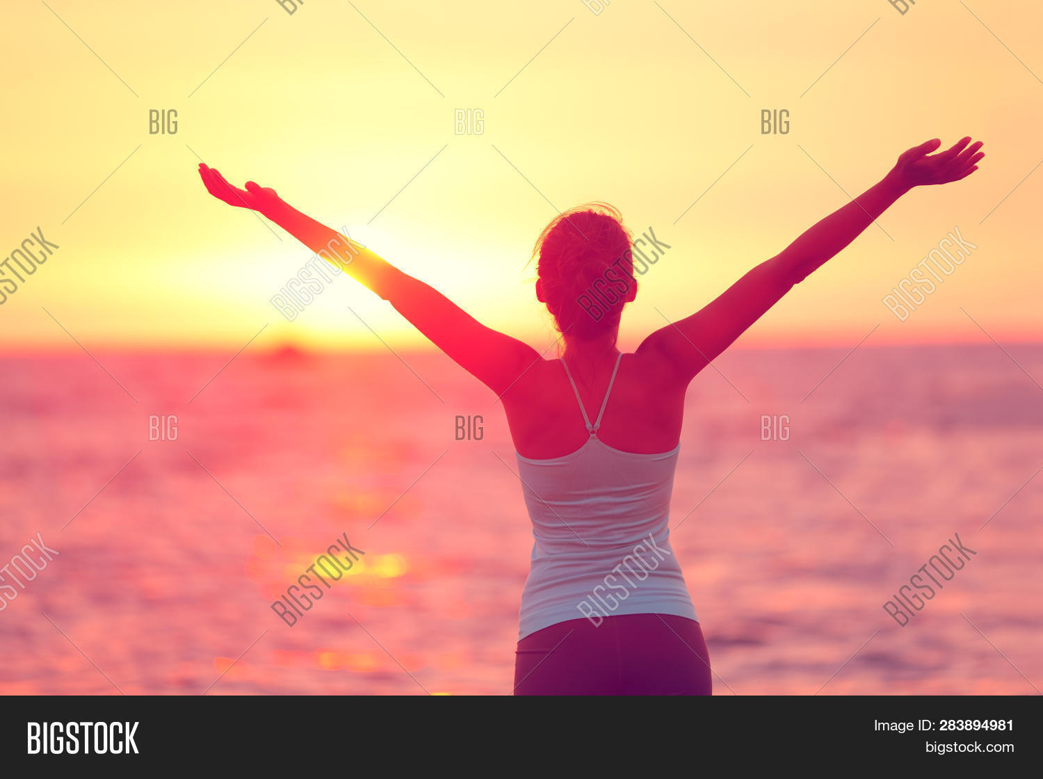 Wellness, well-being and happiness concept. Silhouette of woman with open arms raised to the sky on
