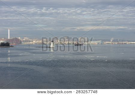 Ice and receding fog drifting past Palmer Island lighthouse in New Bedford harbor stock photo
