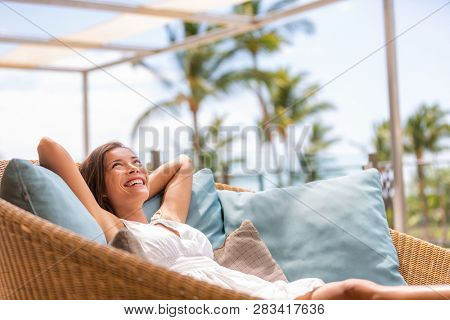 Luxury hotel home living woman relax enjoying sofa furniture of outdoor patio. Beautiful young multi