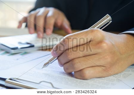 Accountant working on calculator to calculate accounting and business finance plan sales. Business accounting, business investment advisor consulting on the financial report, plan a marketing plan at business office. Business accounting plan concept. stock photo