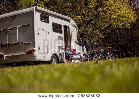 Woman relaxes and reads a book near the camping . Caravan car Vacation. Family vacation travel, holiday trip in motorhome RV. stock photo