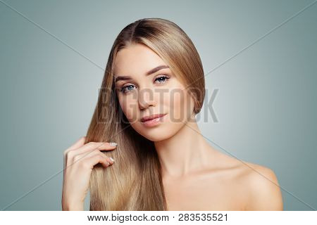 Perfect blonde woman showing her long healthy straight hair portrait. Hair care and hair straightening concept stock photo