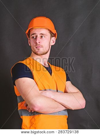 Man in helmet, hard hat hold arms crossed on chest, black background. Worker, contractor, builder on strict face with muscular biceps. Builder in helmet posing confidently. Strong builder concept stock photo